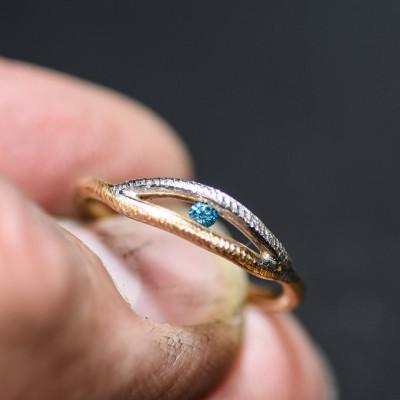 Ring af filet tråd i 2 farvet 14 karat guld isat blå brillant i spændfatning (01/20)